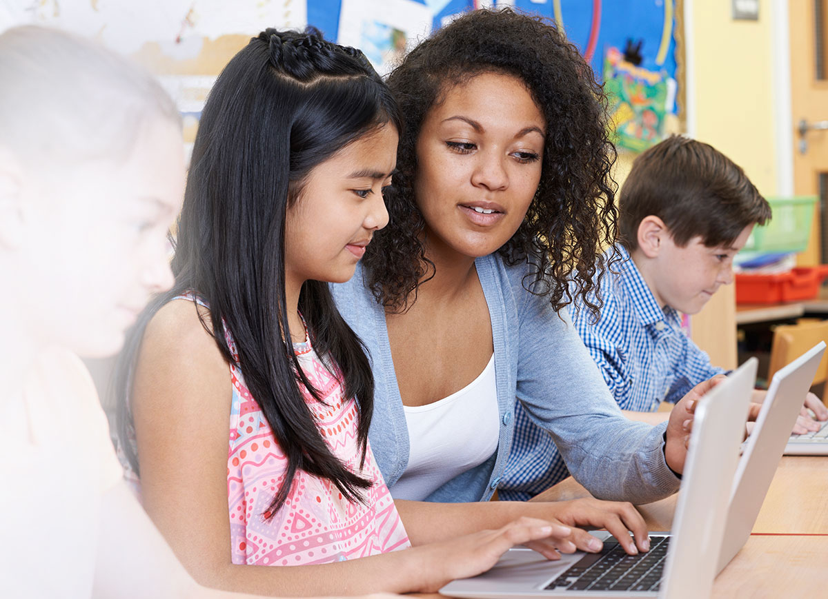 young black woman teaching child on computer in classroom