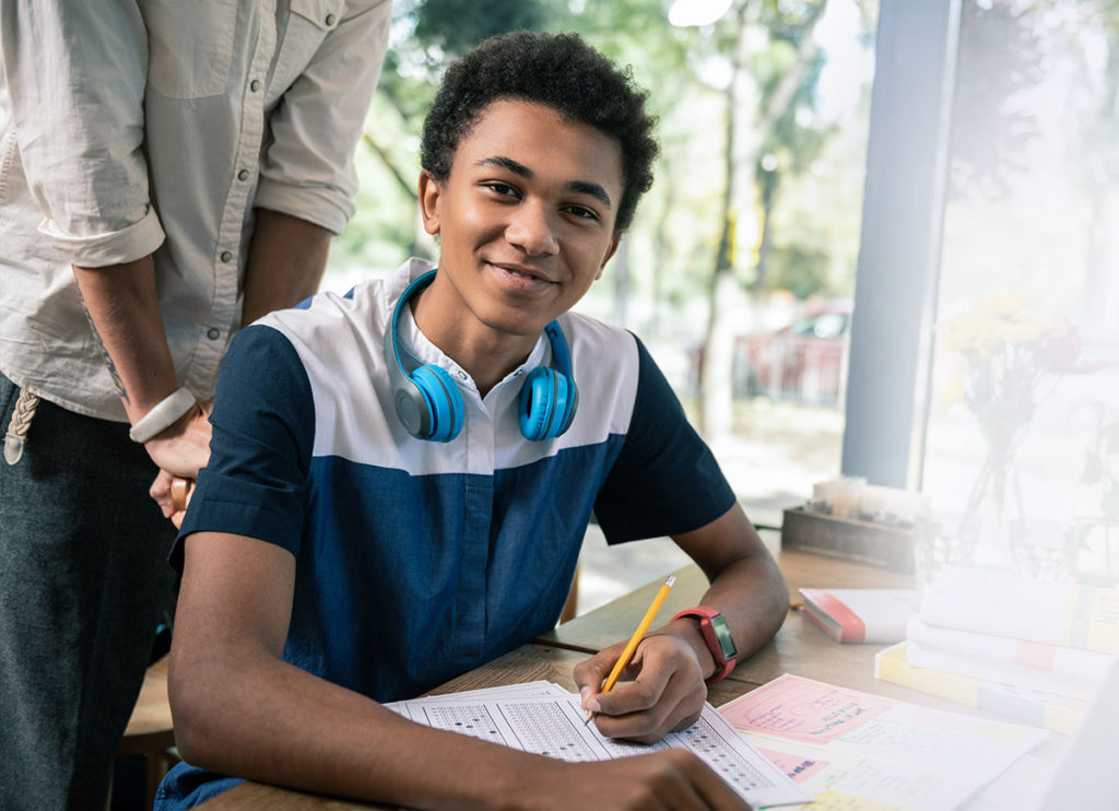 young black man smiling while taking a test at school